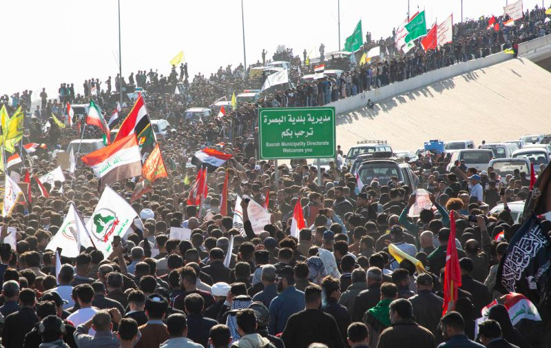 Iraqi mourners gather at the Shaheed Mohammed Baqir al-Sadr Bridge in Basra, Iraq, on Jan. 7, 2019, as they welcome the body of Abu Mahdi al-Muhandis, the slain chief of Hashed al-Shaabi, an Iraqi paramilitary force with close ties to Iran.