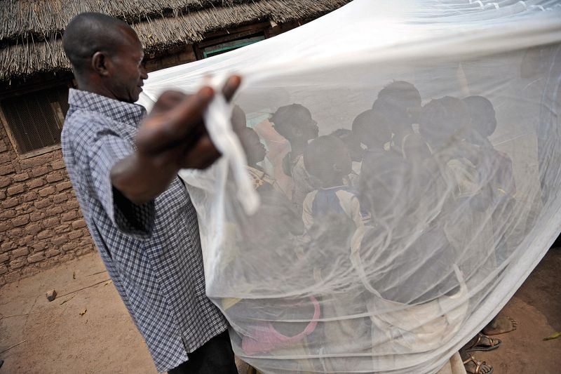 Children learn how to use an insecticide-treated net to prevent malaria exposure in South Sudan on April 2, 2009.