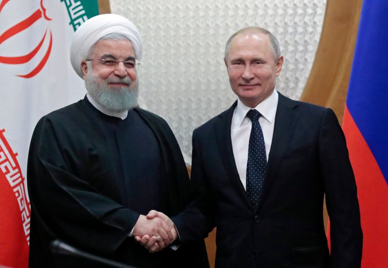 Russian President Vladimir Putin shaking hands with his Iranian counterpart Hassan Rouhani.