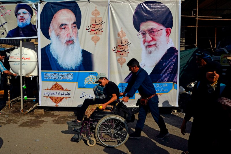 Shiite Muslim pilgrims walk in front of posters of Iran's Supreme Leader Ayatollah Ali Khamenei, the spiritual leader of the Shiite community Grand Ayatollah Ali Sistani, and the leader of Lebanon's Hezbollah movement Hasan Nasrallah during their procession from the holy Iraqi city of Najaf to the central shrine city of Karbala on Oct. 12, 2019.