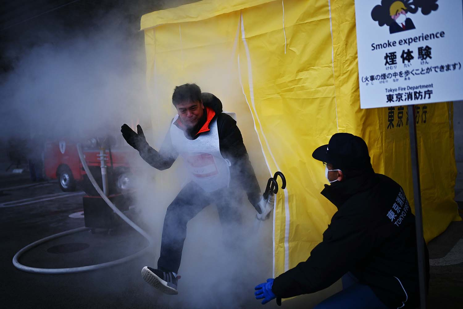 "Participants attend a ""smoke experience"" to see what it is like to walk through smoke during a disaster preparedness drill organized by the Tokyo Metropolitan Government at the Musashino Forest Sports Plaza, the venue for some events at the upcoming Tokyo 2020 Olympics, on Jan. 28. CHARLY TRIBALLEAU/AFP via Getty Images"