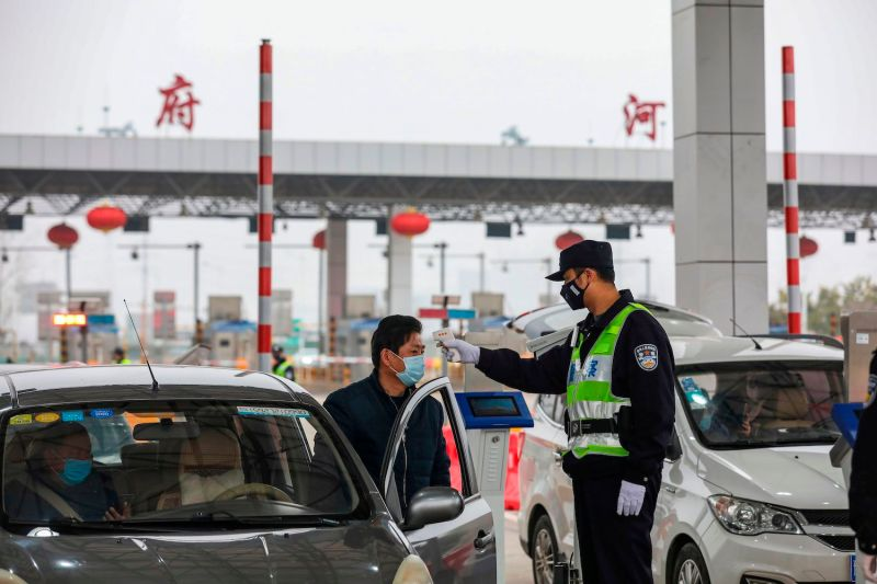 A police officer checks the temperature of a driver at a highway in Wuhan, China, on Jan. 24, 2020.