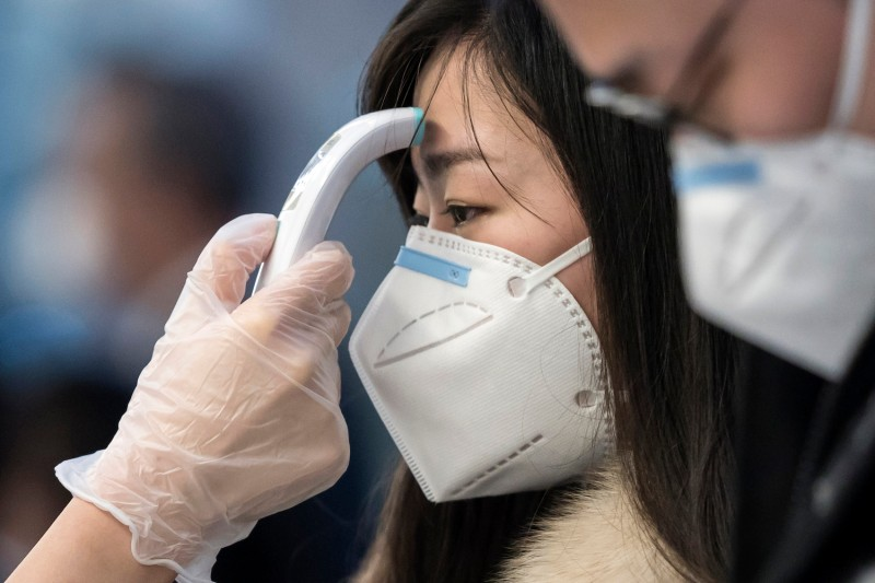 A passenger receives a temperature check before taking a flight bound for Wuhan, China, at Haneda airport on Jan. 31, 2020, in Tokyo, Japan.