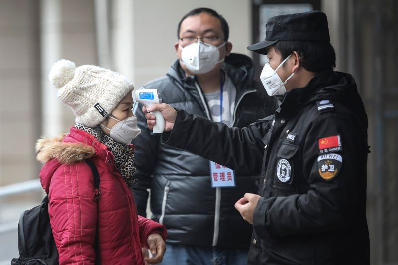 Security officials check the temperature of passengers in Wuhan, China, on Jan. 22.