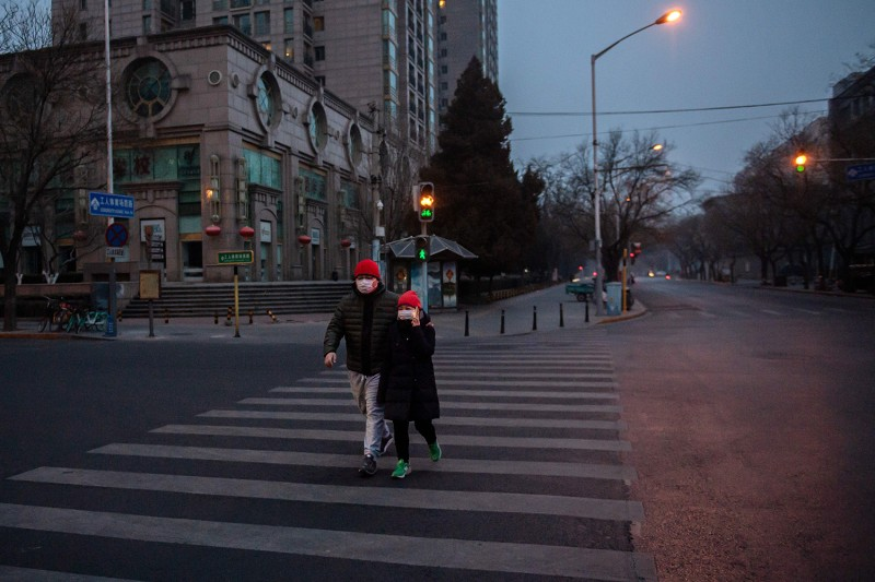 A couple wearing protective masks to help stop the spread of the Wuhan virus walk in Beijing on Jan. 28.