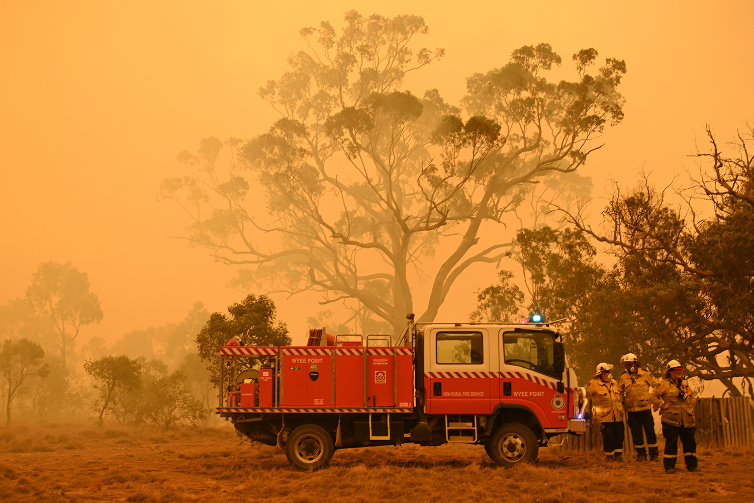 Firefighters protect a property from bushfires burning near the town of Bumbalong south of Canberra, Australia, on Feb. 1. PETER PARKS/AFP via Getty Images