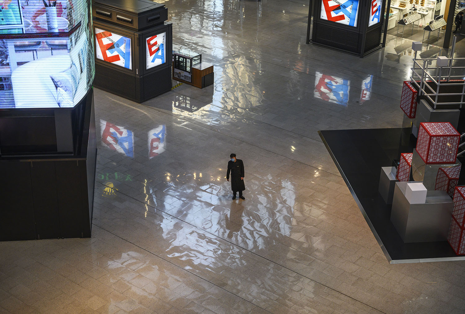 A Chinese security guard wears a protective mask as he stands in a nearly empty shopping mall in Beijing on Feb. 22.
