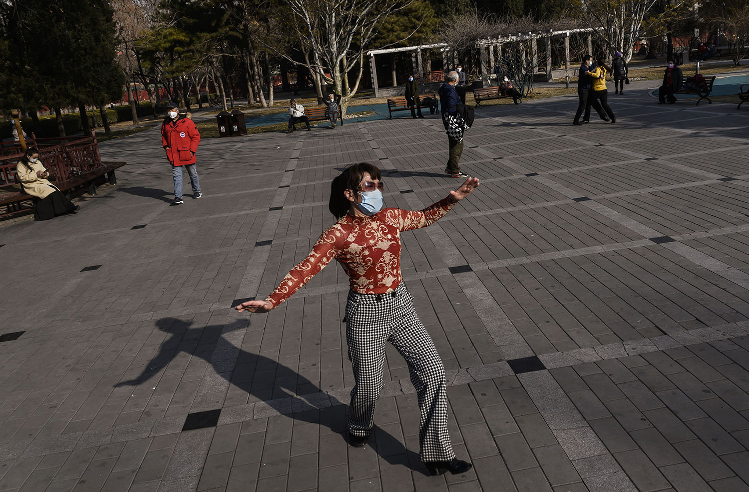 A Chinese woman wears a protective mask as she dances in a sparsely attended park in Beijing on Feb. 23.