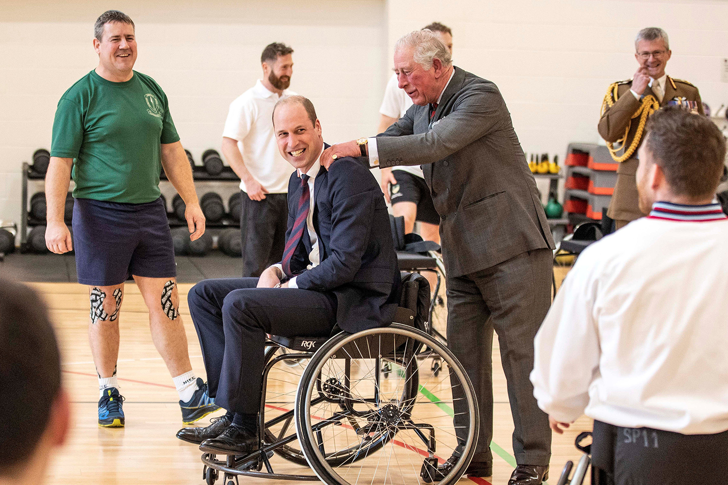 Britain's Prince Charles consoles his son Britain's Prince William after he threw a basketball from a wheelchair but failed to get it into the hoop during their visit to the Defence Medical Rehabilitation Centre in Loughborough, central England, on Feb. 11. RICHARD POHLE/AFP via Getty Images