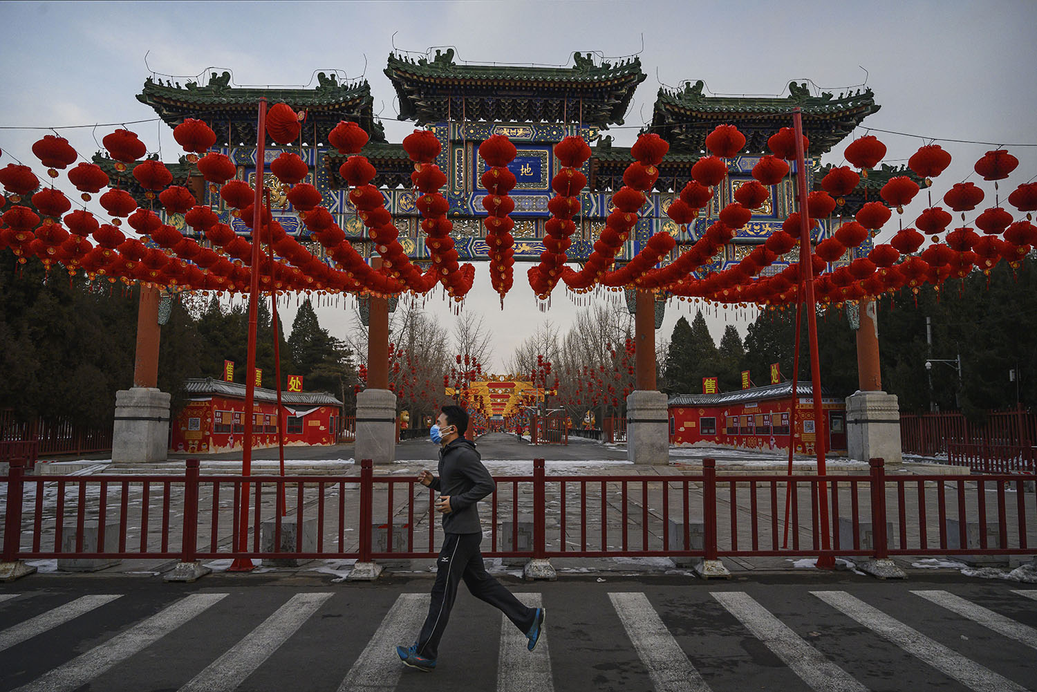 A man wears a protective mask as he runs past red lanterns at a canceled Spring Festival event at a park in Beijing on Feb. 8.