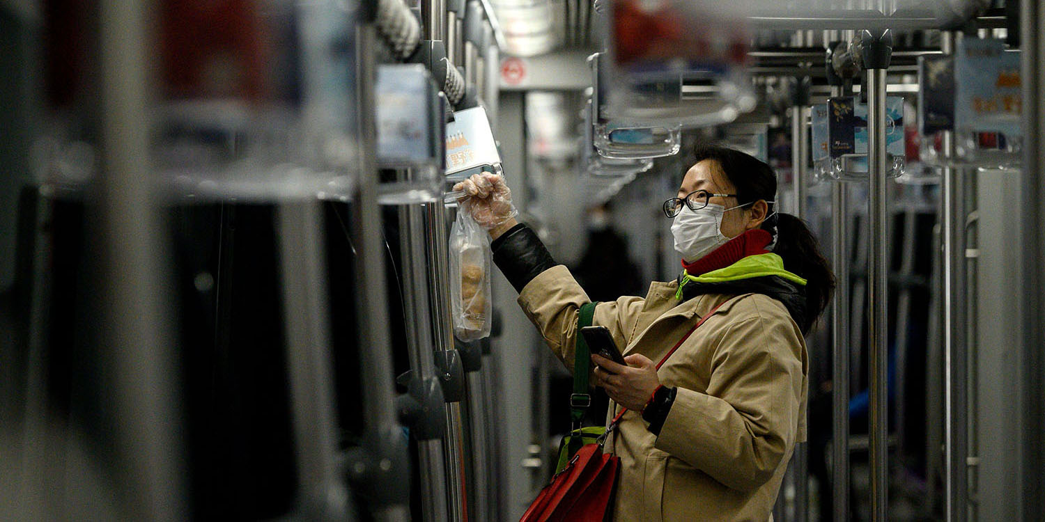 A woman wearing a protective face mask uses her cell phone while riding a train in Shanghai on Feb. 20.