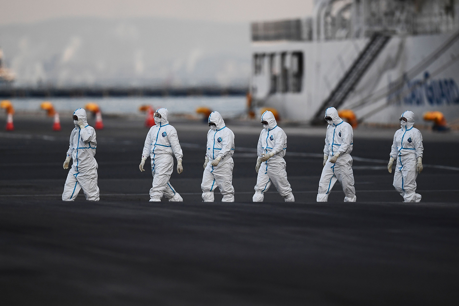 People wearing protective suits walk from the Diamond Princess cruise ship n Yokohama on Feb. 10. CHARLY TRIBALLEAU/AFP via Getty Images