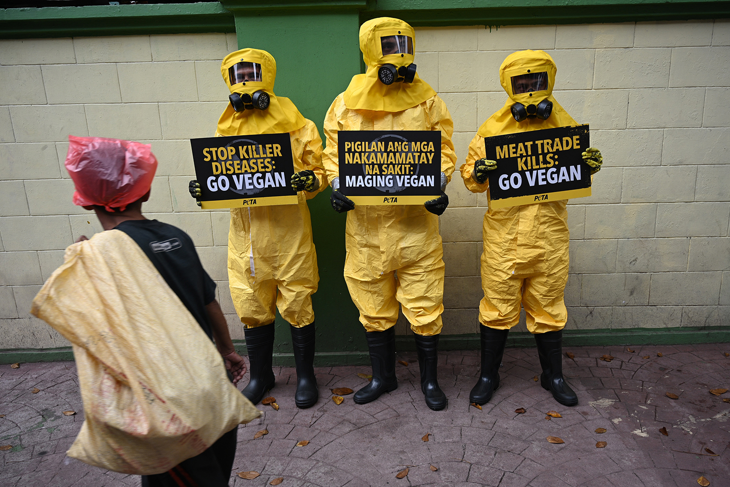 Members of People for the Ethical Treatment of Animals (PETA) wear biohazard suits and hold signs during a protest in front of the department of health in Manila, Philippines, on Feb. 13. TED ALJIBE/AFP via Getty Images