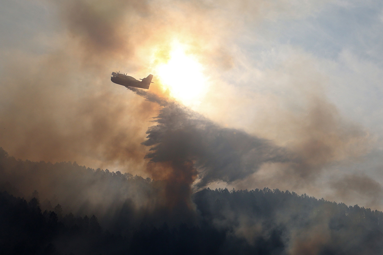 A plane drops water onto a blaze along the l'Arone Pass in the Bavella mountains in Quenza on the French Mediterranean Island of Corsica, after strong winds from storm Ciara caused wildfires to spread on the island, on Feb. 12. PASCAL POCHARD-CASABIANCA/AFP via Getty Images