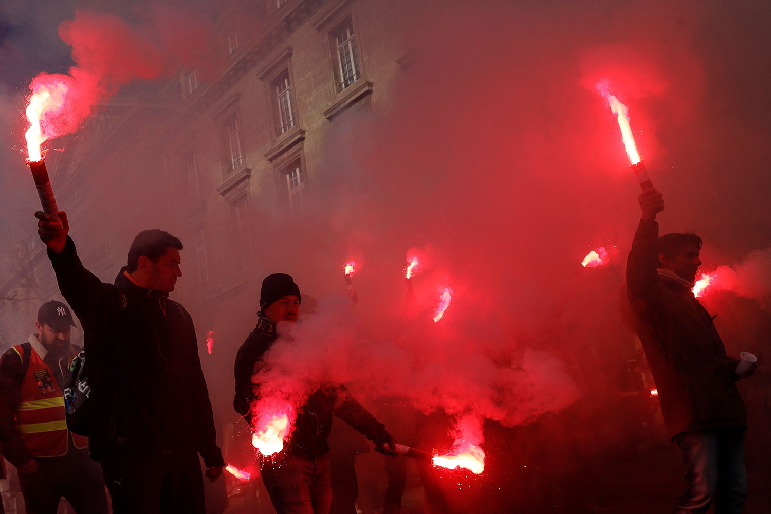 Protesters hold burning flares  during a demonstration against the French government's plan to overhaul the country's retirement system in Paris on Feb. 6. THOMAS SAMSON/AFP via Getty Images