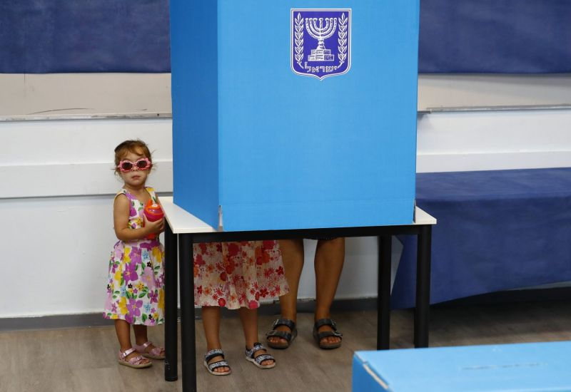 Israeli children accompany their father during Israel's parliamentary election at a polling station in Rosh Haayin on Sept. 17, 2019.