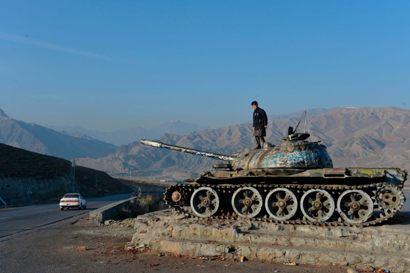 An Afghan boy plays on the wreckage of a Soviet-era tank alongside a road on the outskirts of Kabul on Nov. 28, 2019.