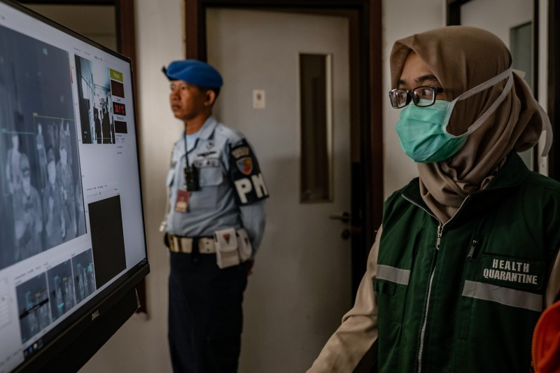 An Indonesian health official monitors as passengers from an international flight have their temperature checked as they pass a thermal scanner monitor upon arrival at the Adisucipto International Airport on January 23, 2020 in Yogyakarta, Indonesia.