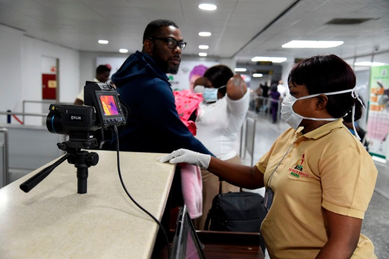 A Port Health Service staff member stands next to a thermal scanner as passengers arrive at the Murtala Mohammed International Airport in Lagos, Nigeria, on Jan. 27, 2019.