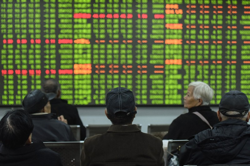 Investors look at a screen showing stock market movements at a securities company in Hangzhou in China's eastern Zhejiang province on Feb. 3.