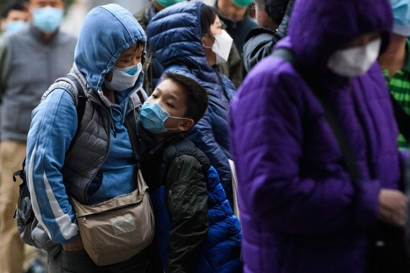A young boy reacts as he and thousands of others line up to purchase face masks from a makeshift stall after waiting for hours in Hong Kong on Feb. 5.