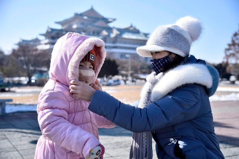 In this photo taken on February 6, 2020, a woman helps her daughter seen wearing a face mask in Pyongyang.