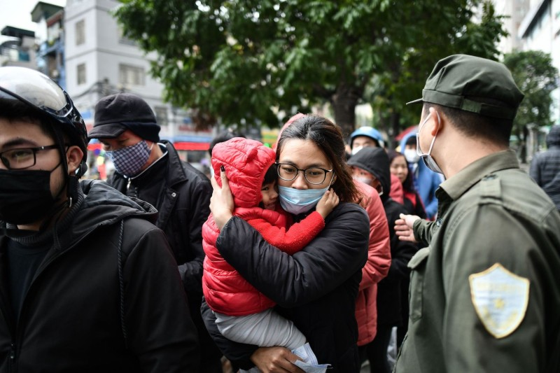 A Vietnamese woman carries her child to receive free protective face masks at a makeshift distribution center amid concerns of a coronavirus outbreak in Hanoi on Feb. 8.