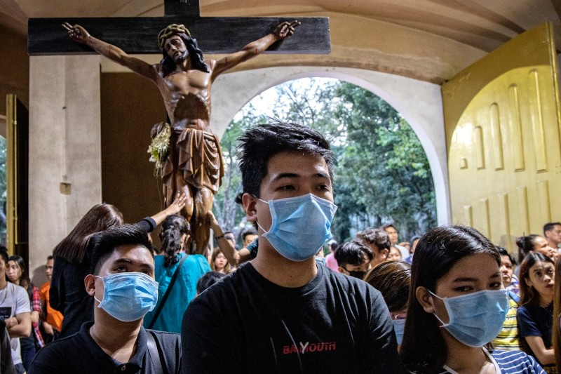 Filipinos wearing face masks attend Sunday Mass at a church in Paranaque, Metro Manila, on Feb. 9.