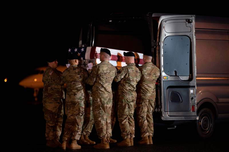 Soldiers lift a coffin into a van during the dignified transfer of two U.S. soldiers killed in Afghanistan