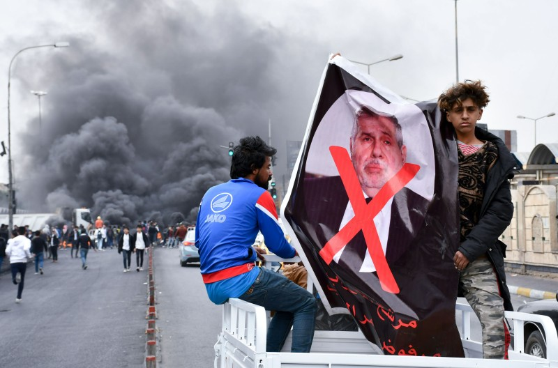 Iraqi demonstrators lift a poster of premier-designate Mohammed Tawfiq Allawi