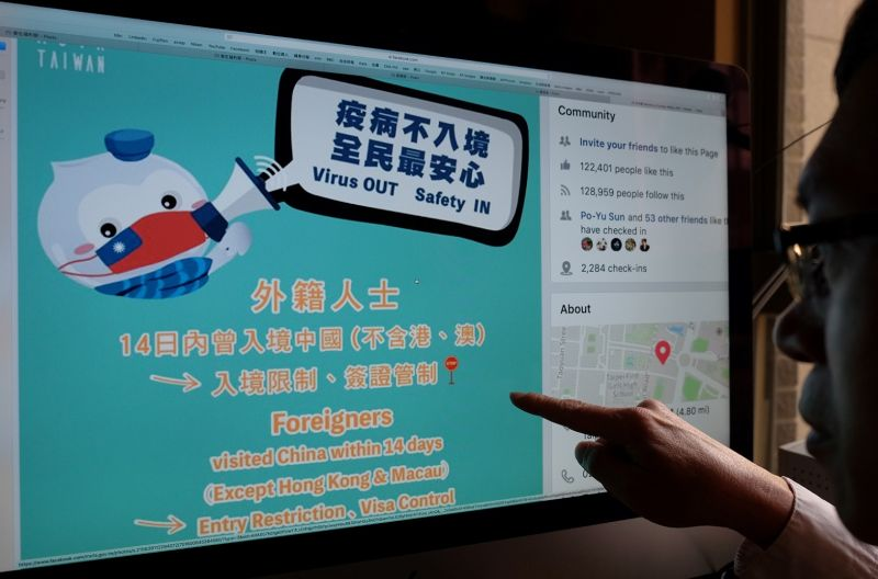 A man points to a webpage promoting prevention of the deadly coronavirus from Taiwan's Ministry of Foreign Affairs Facebook account in Taipei on Feb. 14.