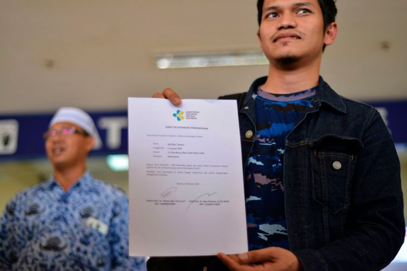 A student shows a letter from the Indonesian health ministry