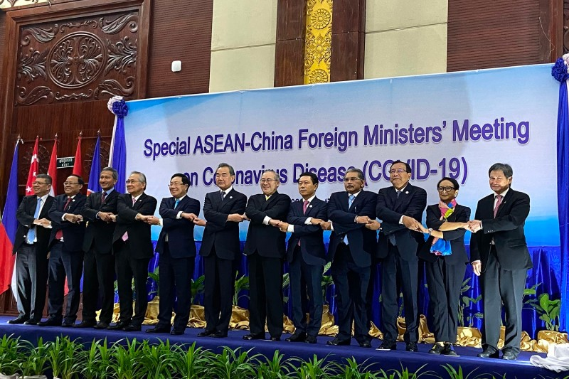 ASEAN foreign ministers shake hands on stage at a summit about the coronavirus called by China in Vientiane, Laos, on Feb. 20.