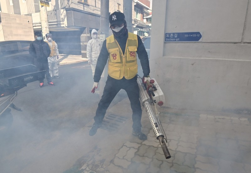 A South Korean health worker sprays disinfectant as part of preventive measures against the spread of the coronavirus at a residential area near the Daegu branch of the Shincheonji Church of Jesus on Feb. 27.