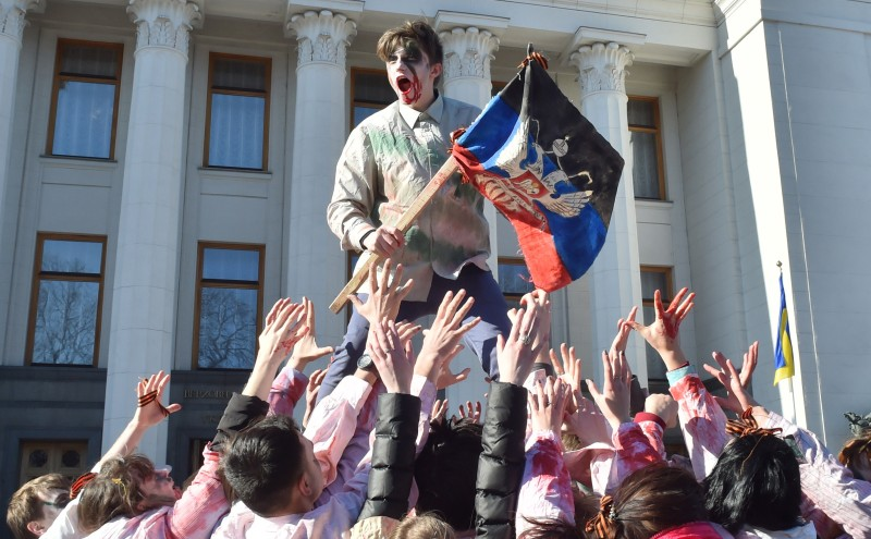 A demonstrator holds a flag of Donetsk People's Republic as he is carried by fellow activists dressed as zombies outside the Ukrainian parliament in Kiev on March 17, 2015.