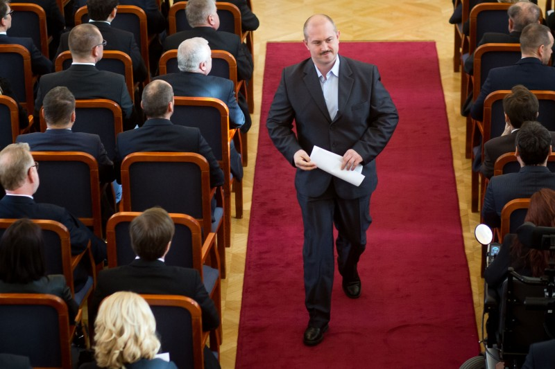 Marian Kotleba, the leader of the right nationalist People's Party-Our Slovakia, walks to his seat during the introduction of delegates to the parliament in Bratislava on March 11, 2016.