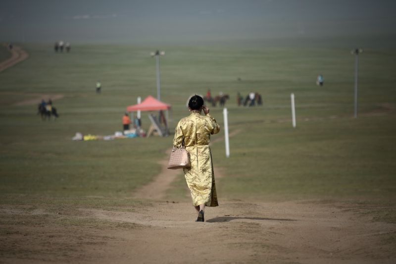 A Mongolian woman walks along a road on the outskirts of Ulaanbaatar on July 13, 2016.