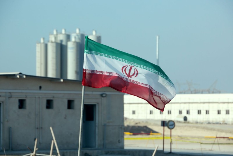 An Iranian flag flies in front of the Bushehr nuclear power plant during an official ceremony to kick-start work on a second reactor at the facility on Nov. 10, 2019.