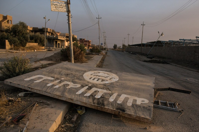 An Islamic State billboard is seen destroyed in the middle of a road in Qaraqosh, Iraq, on Nov. 8, 2016.