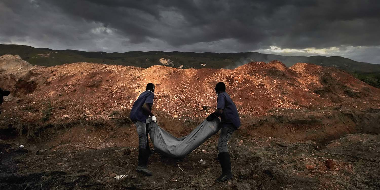Body collectors with the Haitian Ministry of Public Health carry a cholera victim to a mass grave north of Port-au-Prince on Nov. 24, 2010.