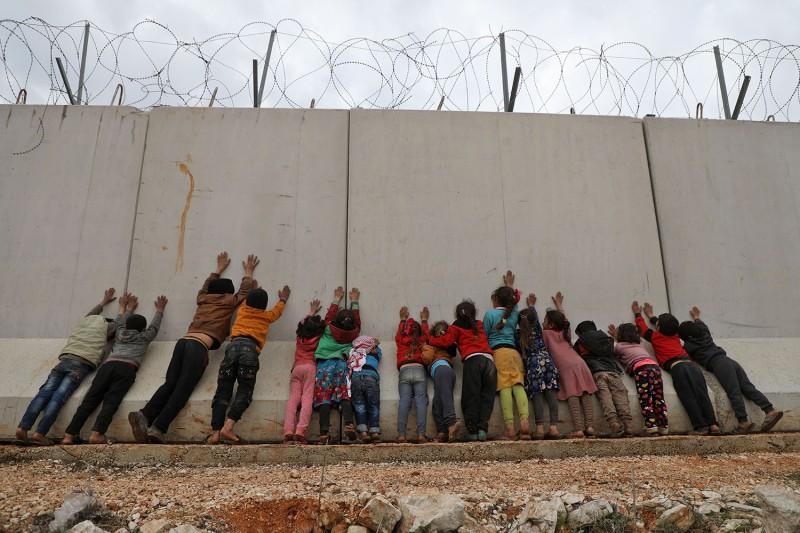 Displaced Syrian children stand by the Turkish border wall at an informal camp in Kafr Lusin village in Syria's northwestern province of Idlib on Feb. 21.