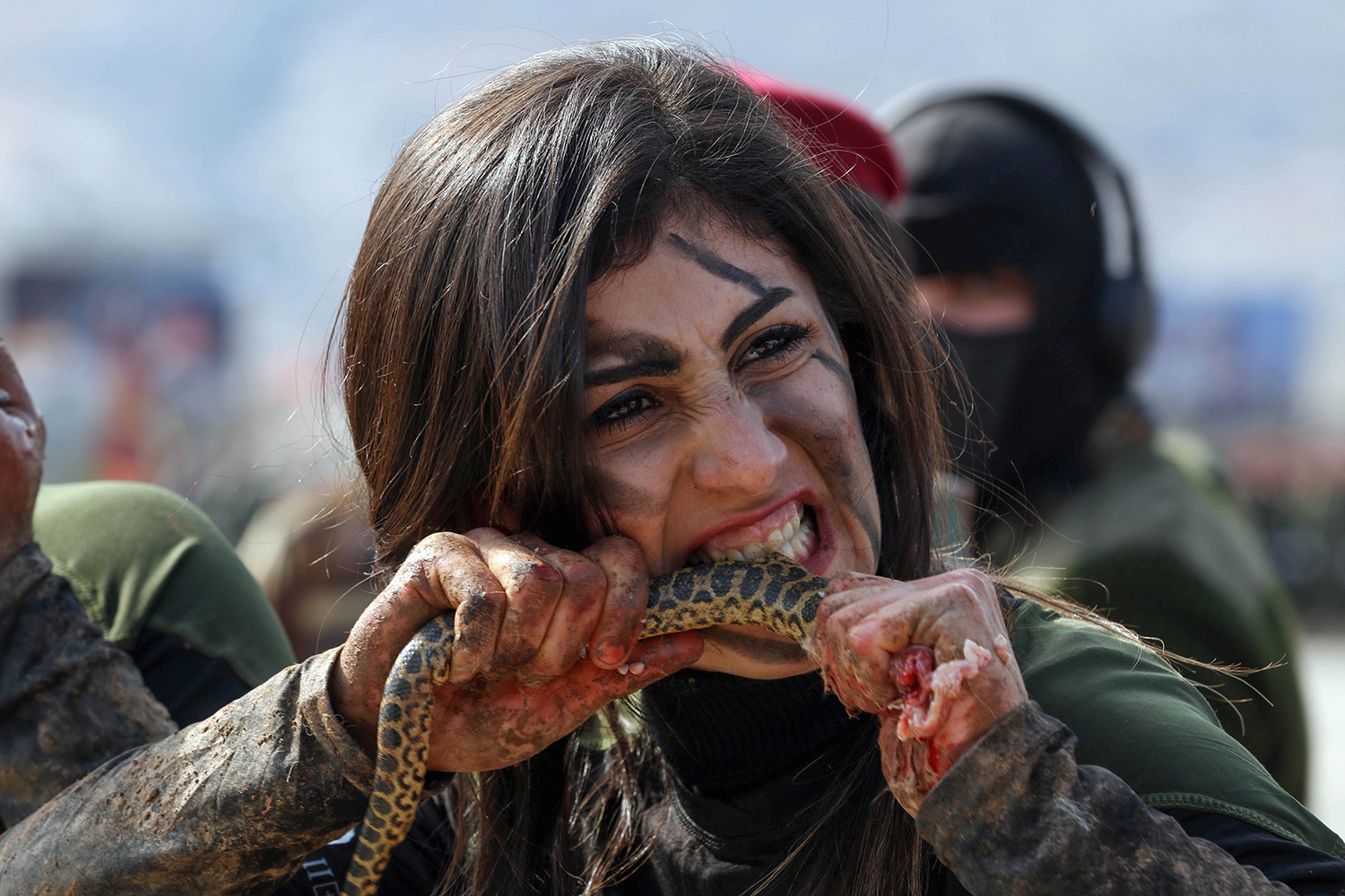 An Iraqi Kurdish Peshmerga officer bites a snake while demonstrating skills during a graduation ceremony in the Kurdish town of Soran, northeast of the capital of Iraq's autonomous Kurdish region Arbil, on Feb. 12. SAFIN HAMED/AFP via Getty Images