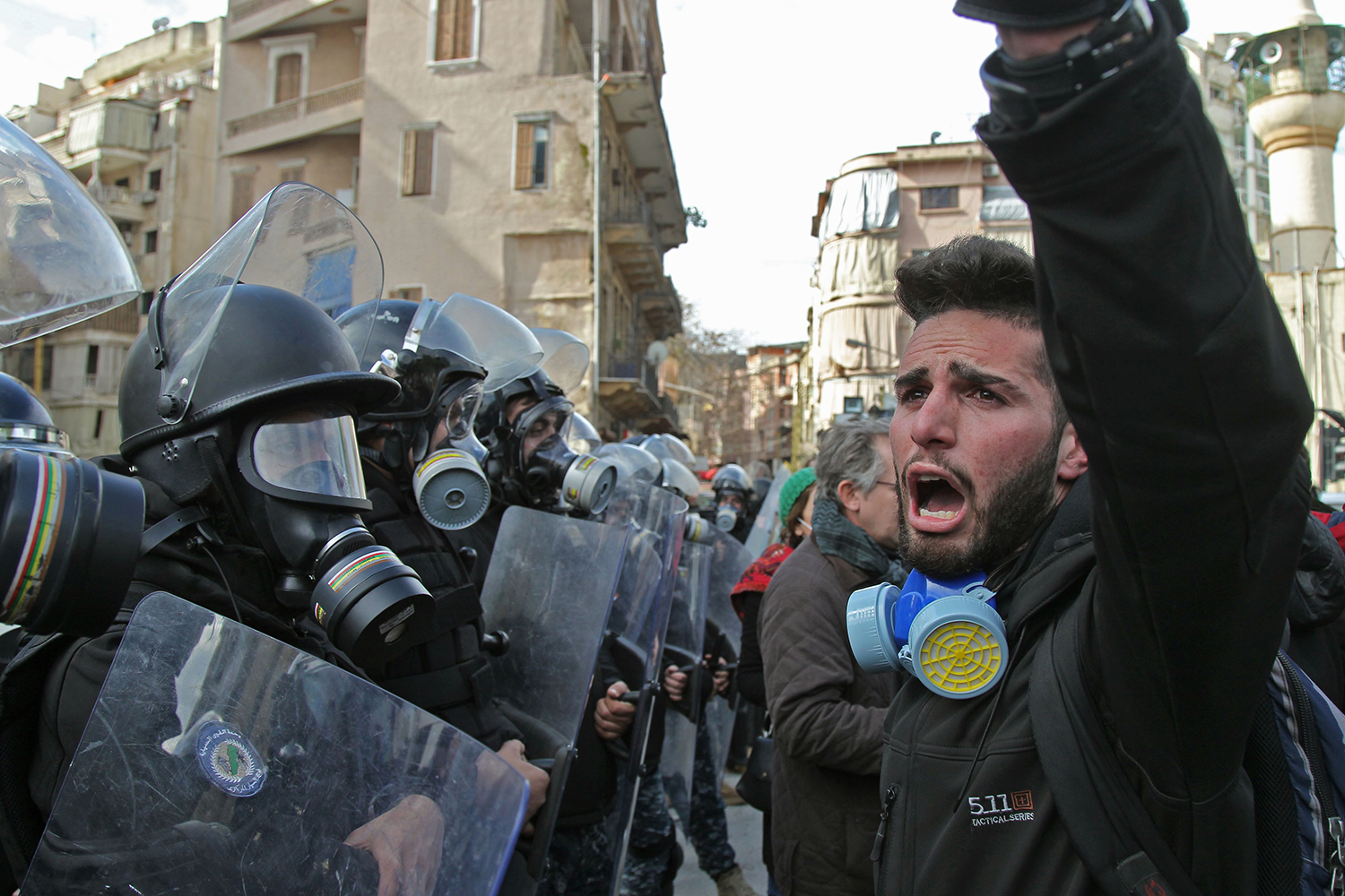 Lebanese protesters chant slogans during clashes with security forces on Feb. 11 as they gather on in the heart of Beirut to stop a confidence vote for a new government, which they say fails to address their demands and cannot rescue the ailing country.  IBRAHIM AMRO/AFP via Getty Images