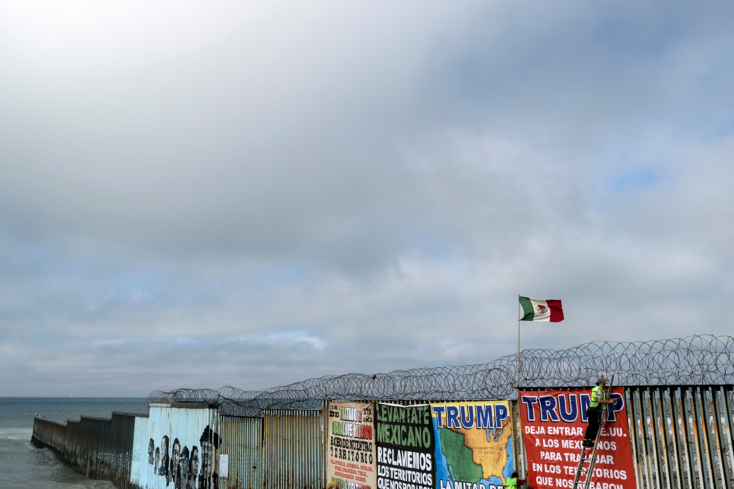 A member of Border Angels hangs a banner protesting U.S. President Donald Trump on the U.S.-Mexico border fence in Playas de Tijuana, Baja California state, Mexico, on Feb. 2.  GUILLERMO ARIAS/AFP via Getty Images