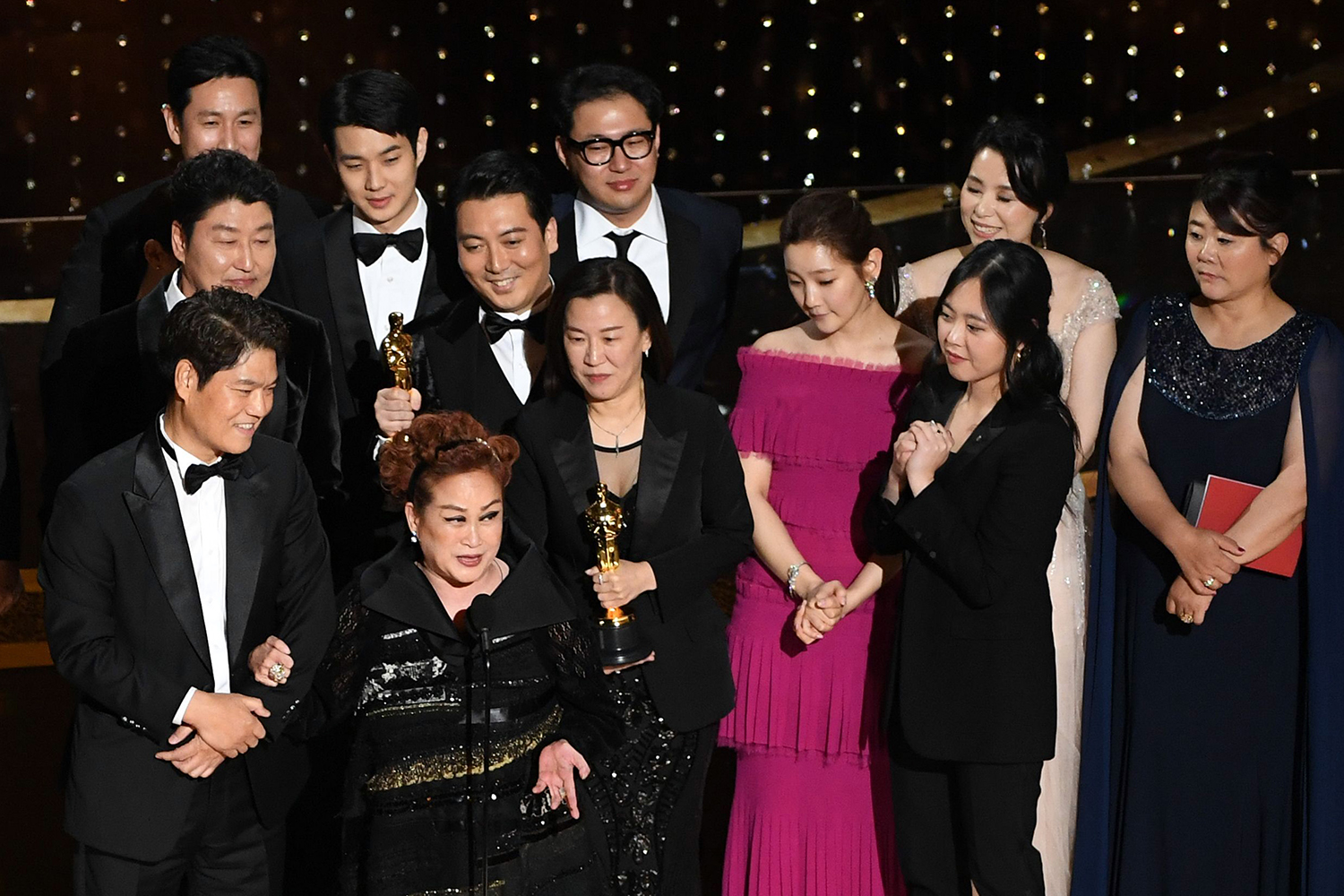 "Executive producer Miky Lee (at the microphone) and the ""Parasite"" team as they accept the Best Picture award during the Academy Awards in Hollywood, California, on Feb. 9."