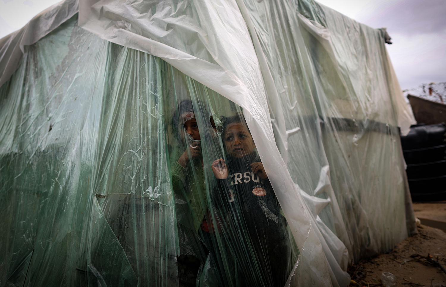 Palestinian children watch the rain from behind nylon sheets covering their family tent in al-Amal neighborhood of Beit Lahia in the northern Gaza Strip on Feb. 8 . MAHMUD HAMS/AFP via Getty Images