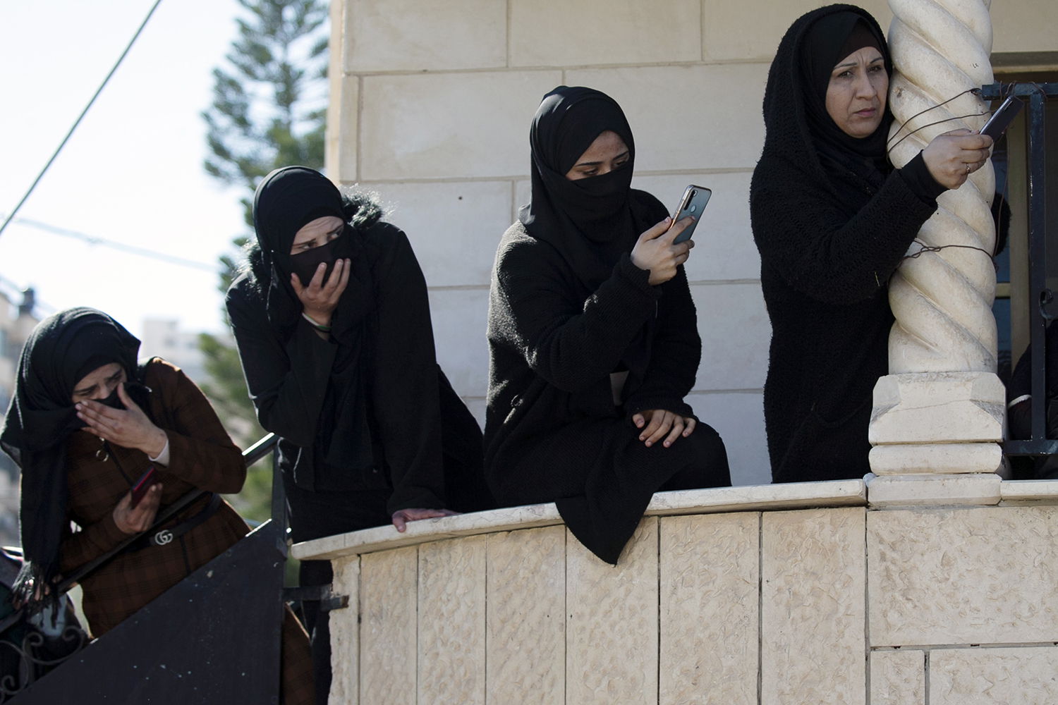 Palestinian women take photos with their phones during the funeral of 19-year-old Yazan Abu Tabikh who was killed by Israeli forces in Jenin, in the north of the occupied West Bank, on Feb. 6. JAAFAR ASHTIYEH/AFP via Getty Images