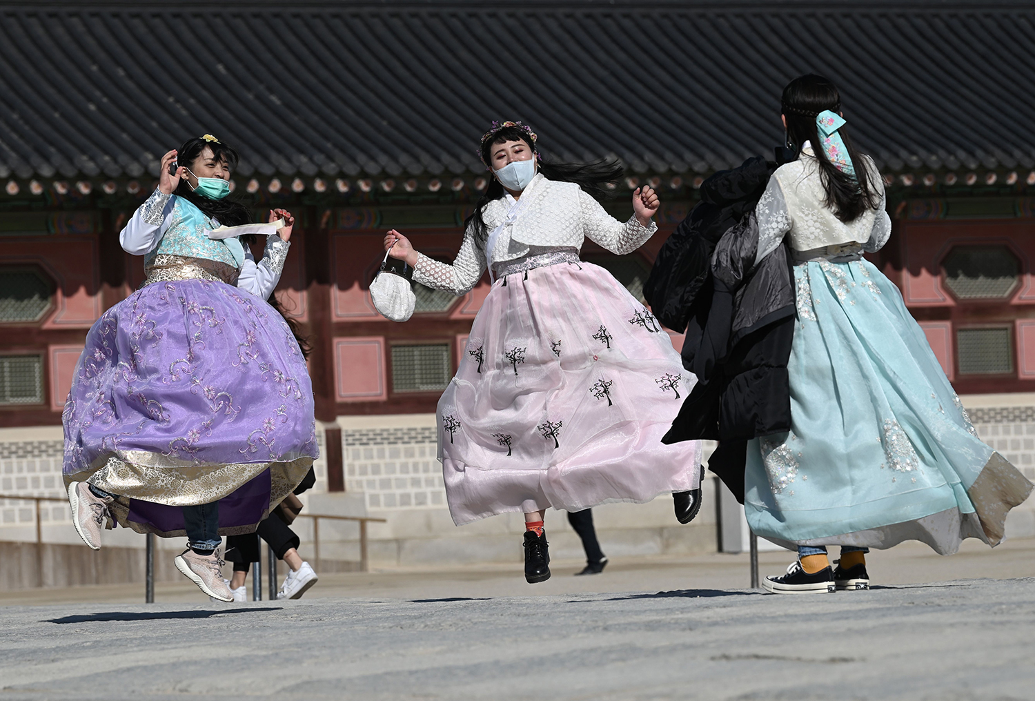 People in traditional Korean hanbok dresses wear face masks as they jump for a souvenir picture at Gyeongbokgung palace in Seoul on Feb. 3. JUNG YEON-JE/AFP via Getty Images