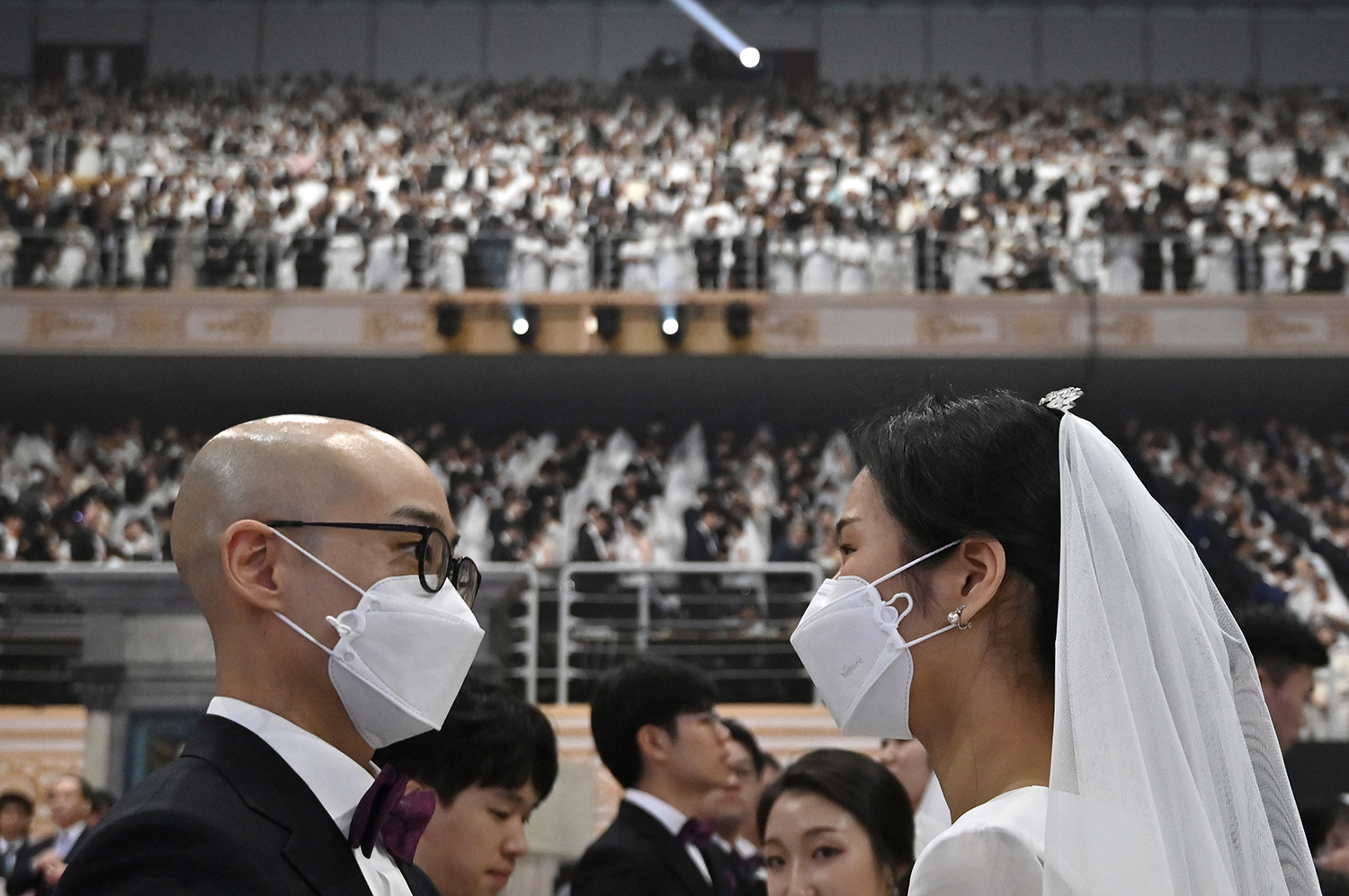 A couple wearing protective face masks attend a mass wedding ceremony organized by the Unification Church at Cheongshim Peace World Center in Gapyeong, South Korea, on Feb. 7. JUNG YEON-JE/AFP via Getty Images