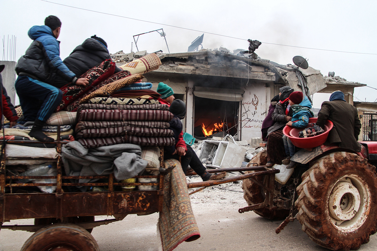 Members of a Syrian family fleeing attacks by pro-regime forces drive past a burning shop in the town of Abin Semaan west of  Aleppo on Feb. 12. IBRAHIM YASOUF/AFP via Getty Images
